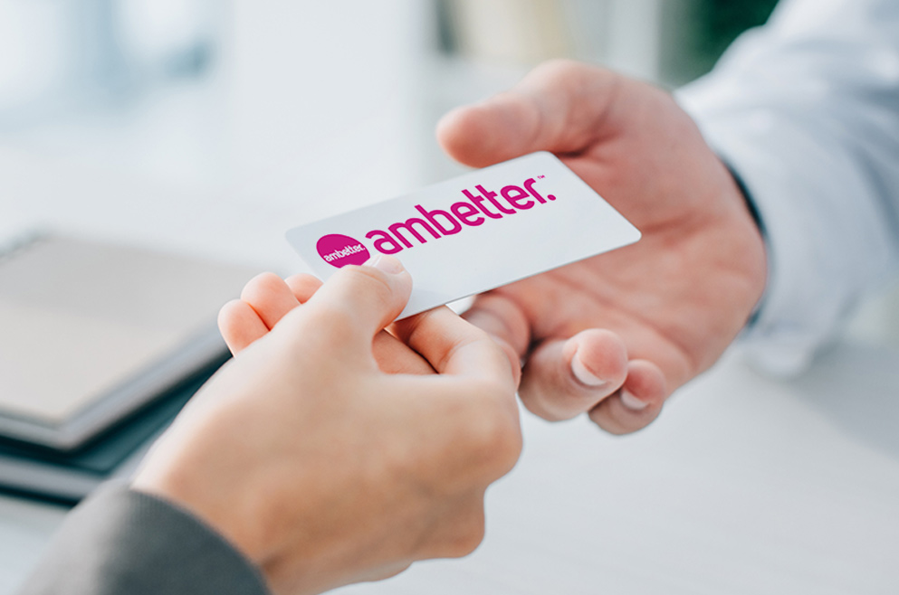 Photo of doctor handing a patient Ambetter card.