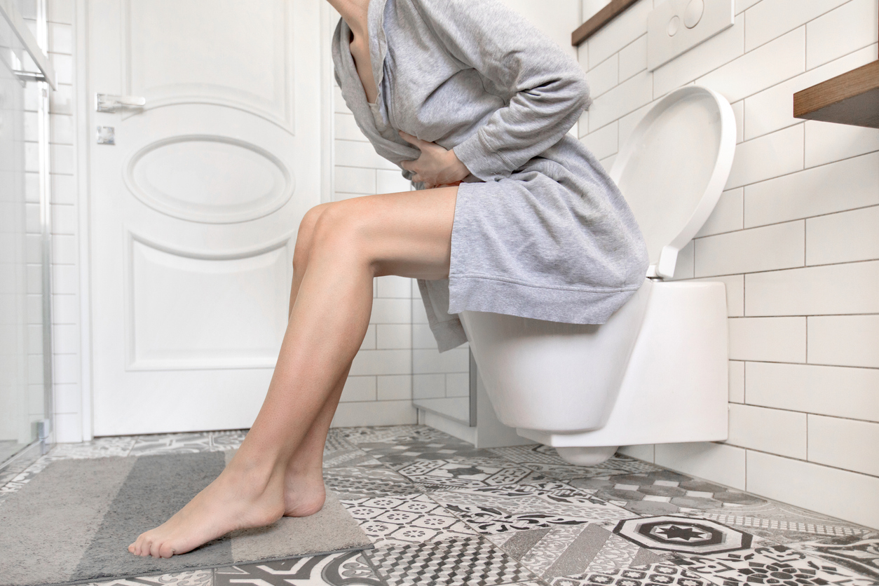 Brunette woman sitting on toilet in the bathroom. She is holding her stomach. Wears a grey dressing-gown.