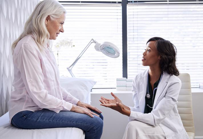 Doctor speaking with woman patient about AVIVA Scarless Labiaplasty and Votiva Vaginal Rejuvenation.