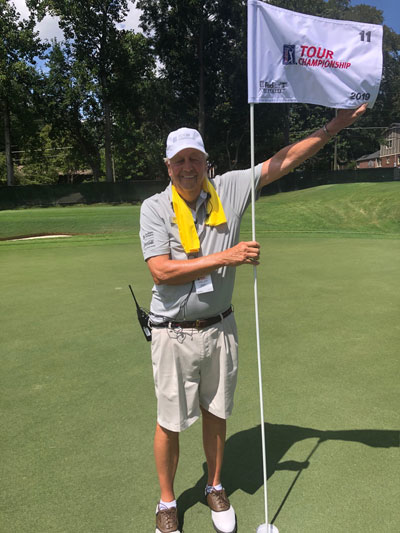 Volunteer, Bob Weyand, holding a TOUR Championship flag at the East Lake golf course.