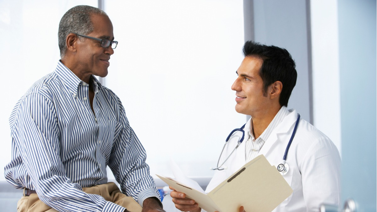 An African American man speaking to a urologist, asking the five questions men should ask about prostate cancer.