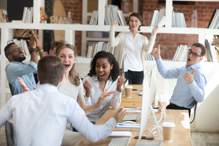 Male worker share good news with multiracial colleagues in shared workplace, diverse employees scream with happiness excited with corporate success or goal achievement, team celebrating win.