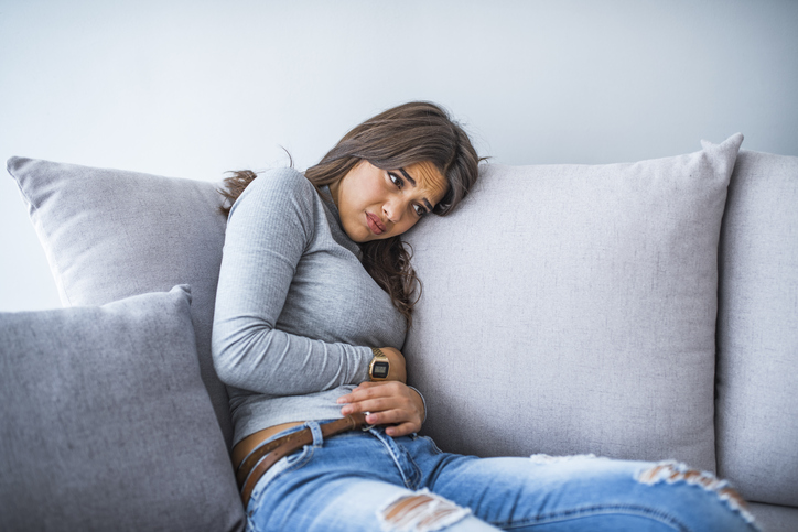 Young woman suffering from abdominal pain while sitting on bed at home. Young woman suffering from abdominal pain at home. Gynecology concept. Young woman in pain lying on couch at home, casual style indoor shoot.
