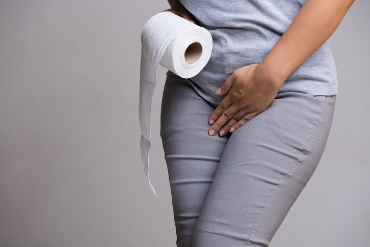 Woman hand holding her crotch lower abdomen and tissue or toilet paper roll. Disorder, Diarrhea, incontinence. Healthcare concept, dealing with overactive bladder.