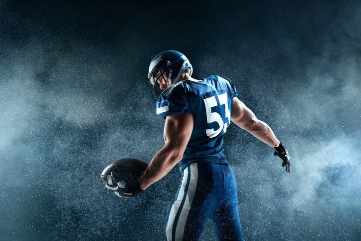 American football, football player standing in dramatic lighting.