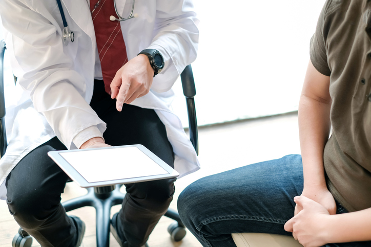 Doctor holding digital tablet talk and explain about the treatment of male patients. Treating patients with prostate cancer. and erectile dysfunction.