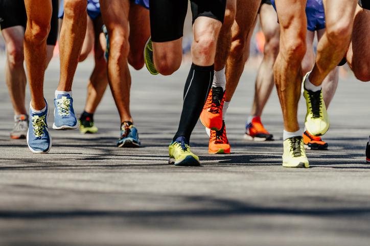 group legs runners athletes run on asphalt road marathon