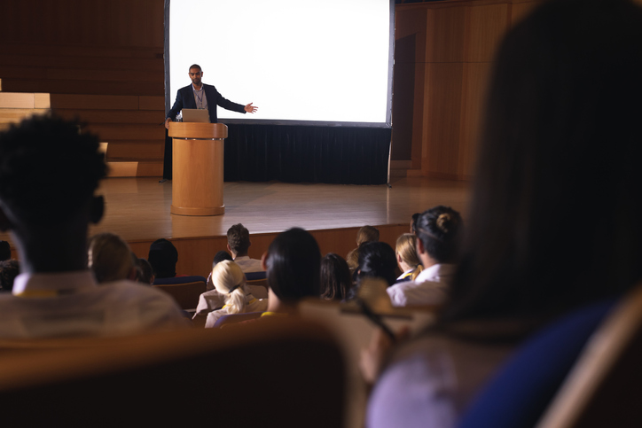 Front view of mixed race businessman giving presentation on white projector in front of the audience.