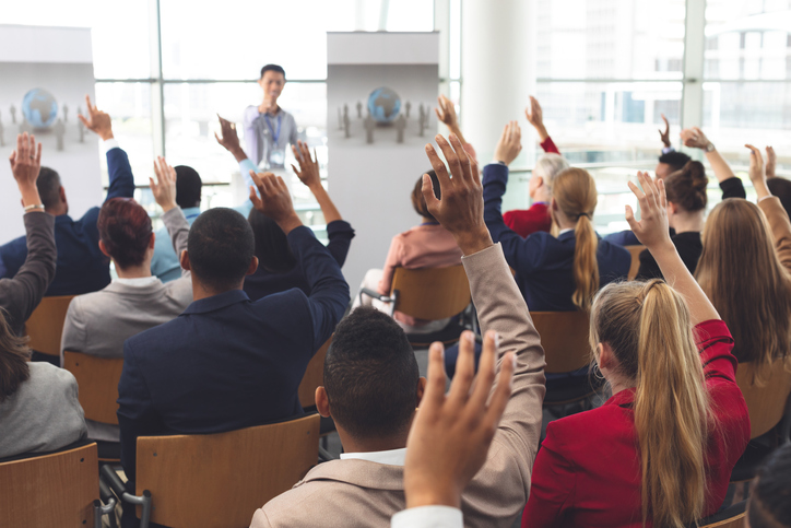 Rear view of diverse business people raising hands while they are sitting in front of Asian businessman at business seminar in office building.