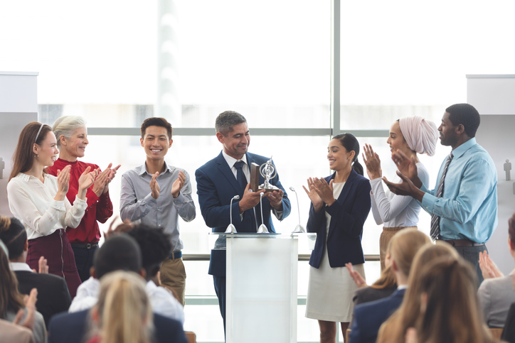 Front view of mixed race businessman holding award on podium with colleagues in front of business professionals at business seminar in office building.