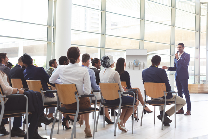 Front view of handsome mixed-race businessman speaking at business seminar with diverse business people listening to him at conference.