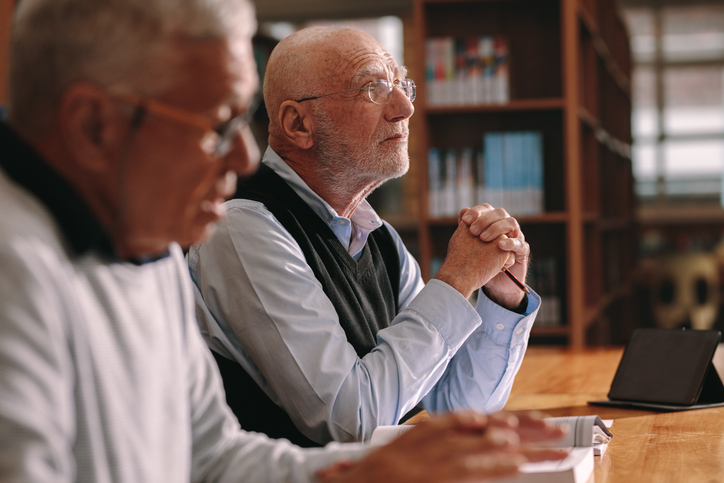 Two senior men sitting in classroom listening to a lecture. Elderly men sitting in a classroom with books and a tablet pc on the table.