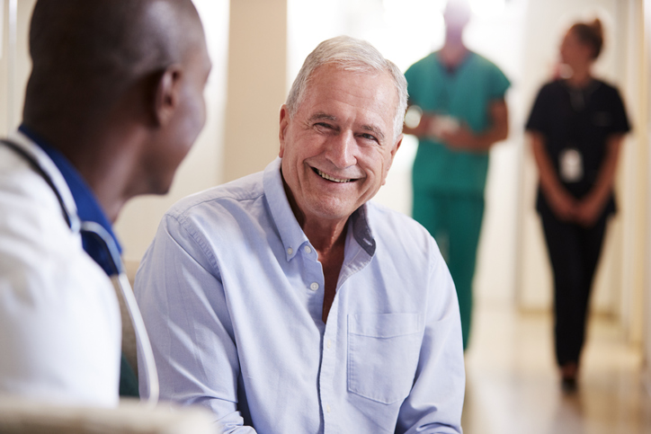 Doctor Welcoming To Senior Male Patient Being Admitted To Hospital, discussing Male Reconstructive Surgery