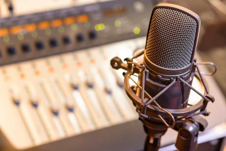 condenser microphone on mixing console background. audio recording concept.
