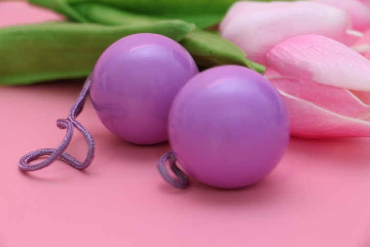 Pink vaginal balls on a pink background. Double vaginal balls. Womans health for kegel exercises. Strengthening the intimate muscles of the vagina.