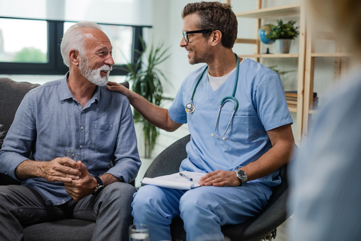 Happy doctor talking to senior male patient while being in a home visit.