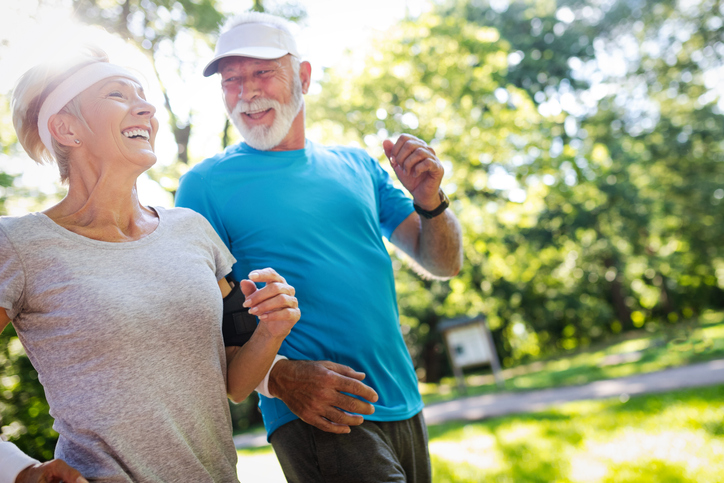 Beautiful senior couple jogging in nature living healthy.