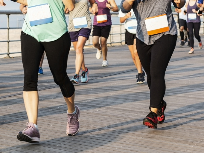 Many runners are running a race on a boardwalk by the beach shot from the waist down.