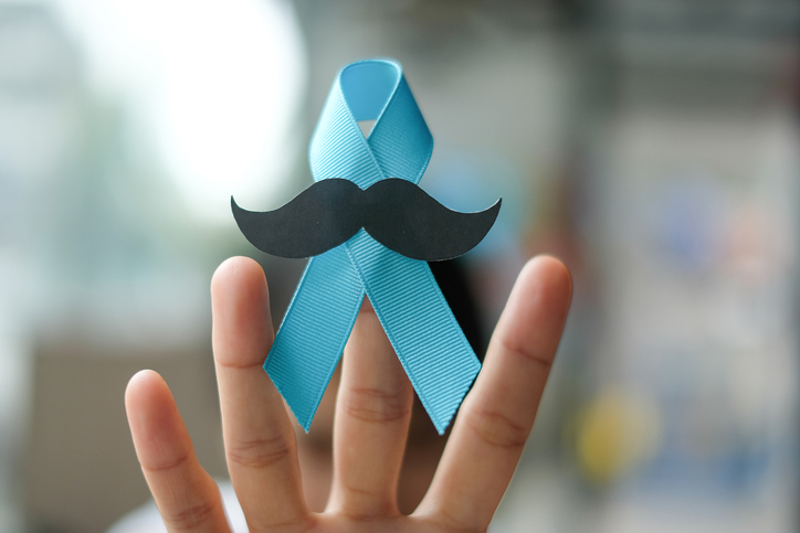 Prostate Cancer Awareness, wonan hand holding light Blue Ribbon with mustache for supporting people living and illness. Men Healthcare and World cancer day concept.