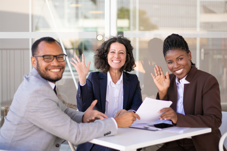 Happy successful business team posing at table and waving hello. Cheerful multiethnic man and women sitting in outdoor cafe and smiling at camera. Team success concept.