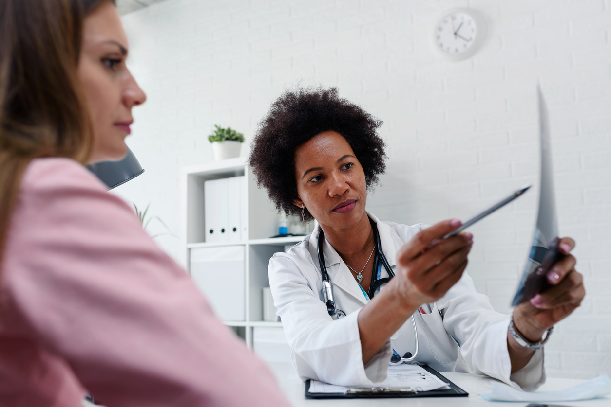 Doctor talking with patient at desk in medical office.