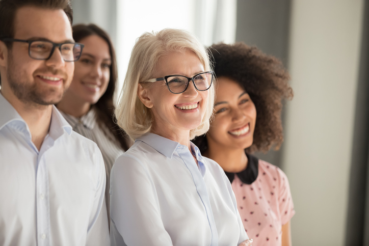 Side view of smiling diverse employees stand in row together posing for group picture in office, happy confident multiethnic team look at camera making photo, showing unity. Teamwork concept
