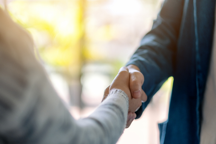Closeup image of two people shaking hands.
