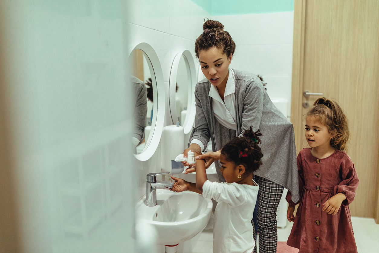 Teacher and little girls washing their hands at the bathroom sink, Breaking the Barriers on Bathroom Passes