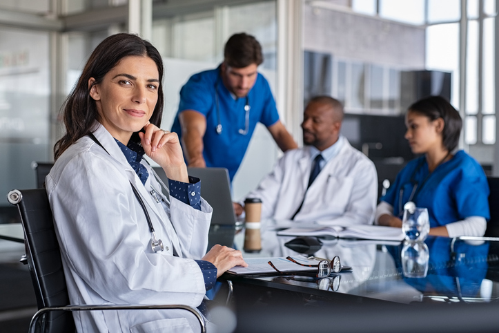 Portrait of mature female doctor sitting in meeting room with specialist and nurses discussing case in background. Successful woman doctor in labcoat and stethoscope in hospital. Smiling pediatrician looking at camera with medical staff brainstorming in background.