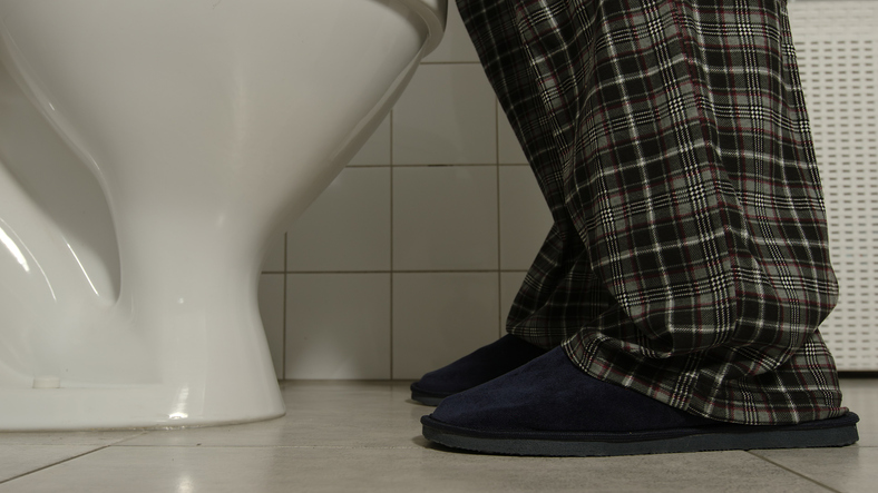 Closeup of male legs in a pajamas and slippers comes to a toilet, wondering Can Drinking Liquids at Night Increase Your Risk for Urologic Problems?