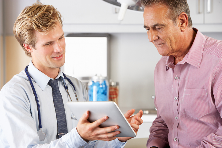 Male Doctor Discussing Records With Senior Patient Using Digital Tablet, discussing Peyronie's Disease .