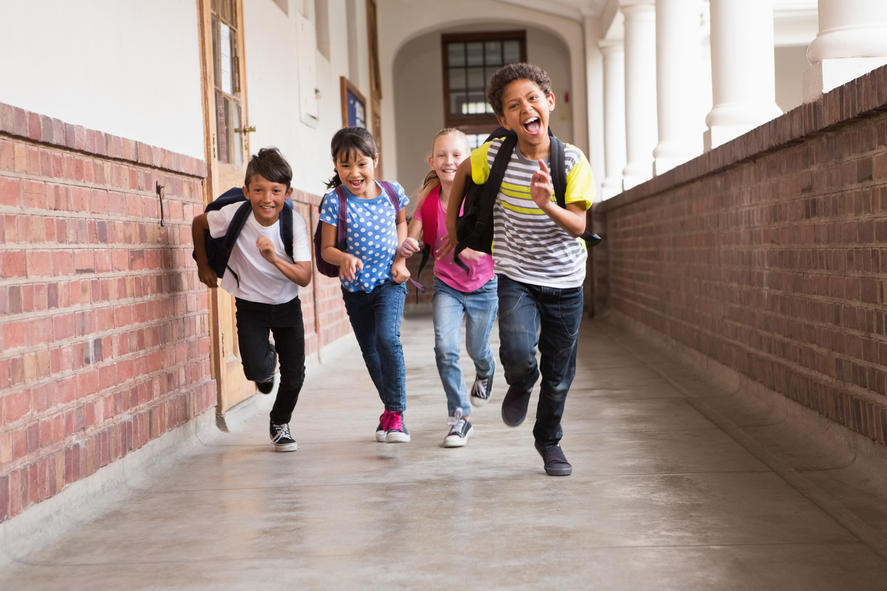 Cute pupils running down the hall at the elementary school, not worried about bedwetting.