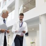 Two Doctors Talking As They Walk Through Modern Hospital, discussing benign Prostatic Hyperplasia