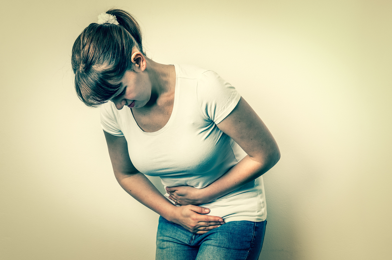 Woman with menstrual pain is holding her aching belly - isolated on white background, wondering why do bladders fall.