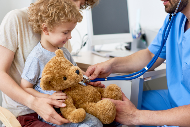 Portrait of adorable curly child sitting on mothers lap in doctors office holding teddy bear toy, with pediatrician listening to heartbeat using stethoscope. child getting checked for hydroceles