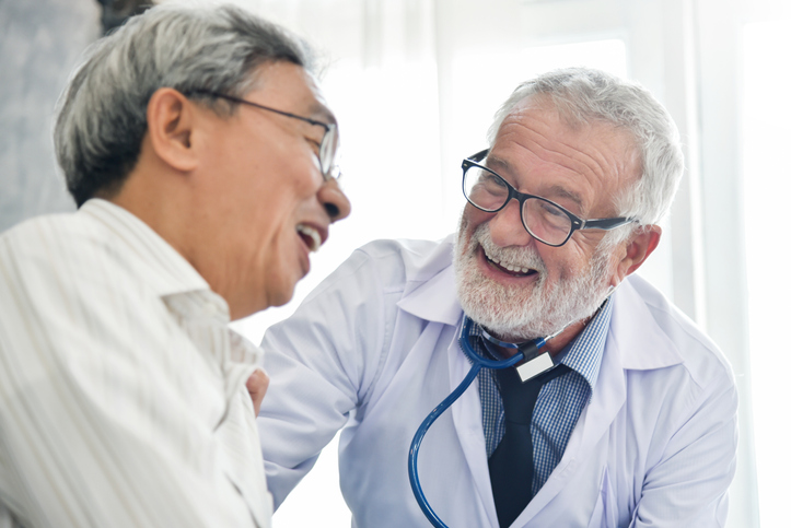 Happiness People. Senior male Doctor and Asian male patient are talking in the medical room together. Smiling, discussing prostate cancer rehabilitation treatments.