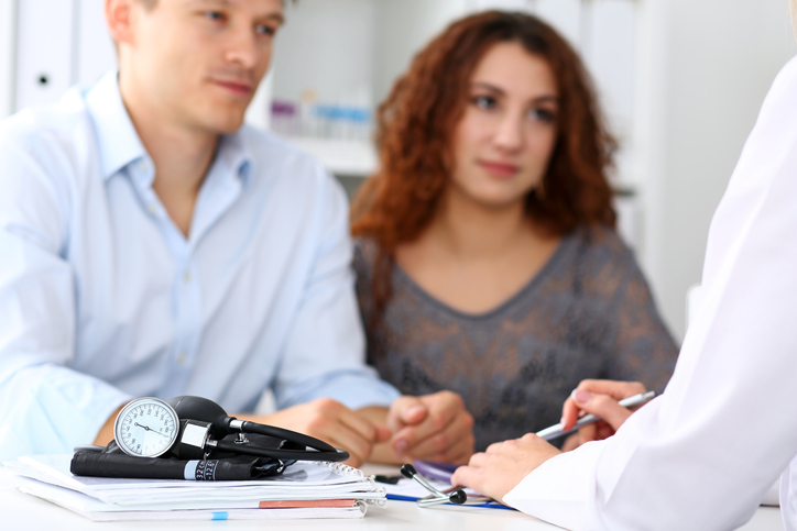 Male and female couple at a doctor's desk, holding hands and discussing Infertility in Males.