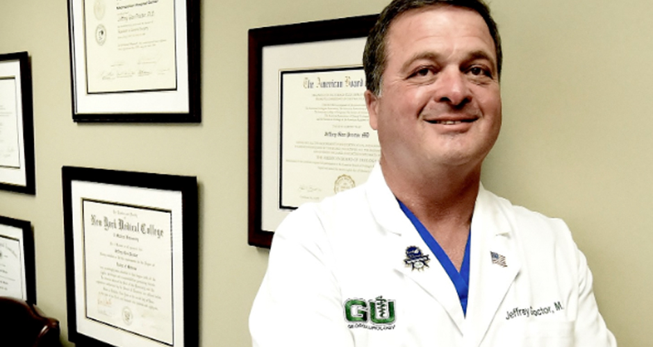 Urologist Dr. Jeffrey Proctor standing in front of his accolades in his office.