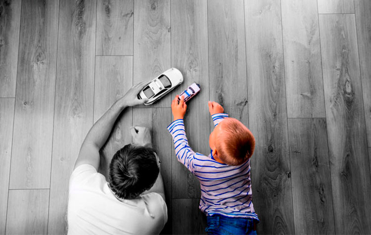 Father and son playing with toy cars on floor