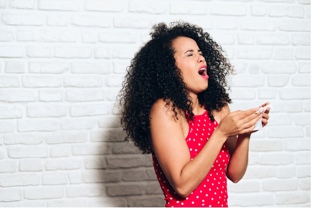 african american woman sneezing, stress urinary incontinence